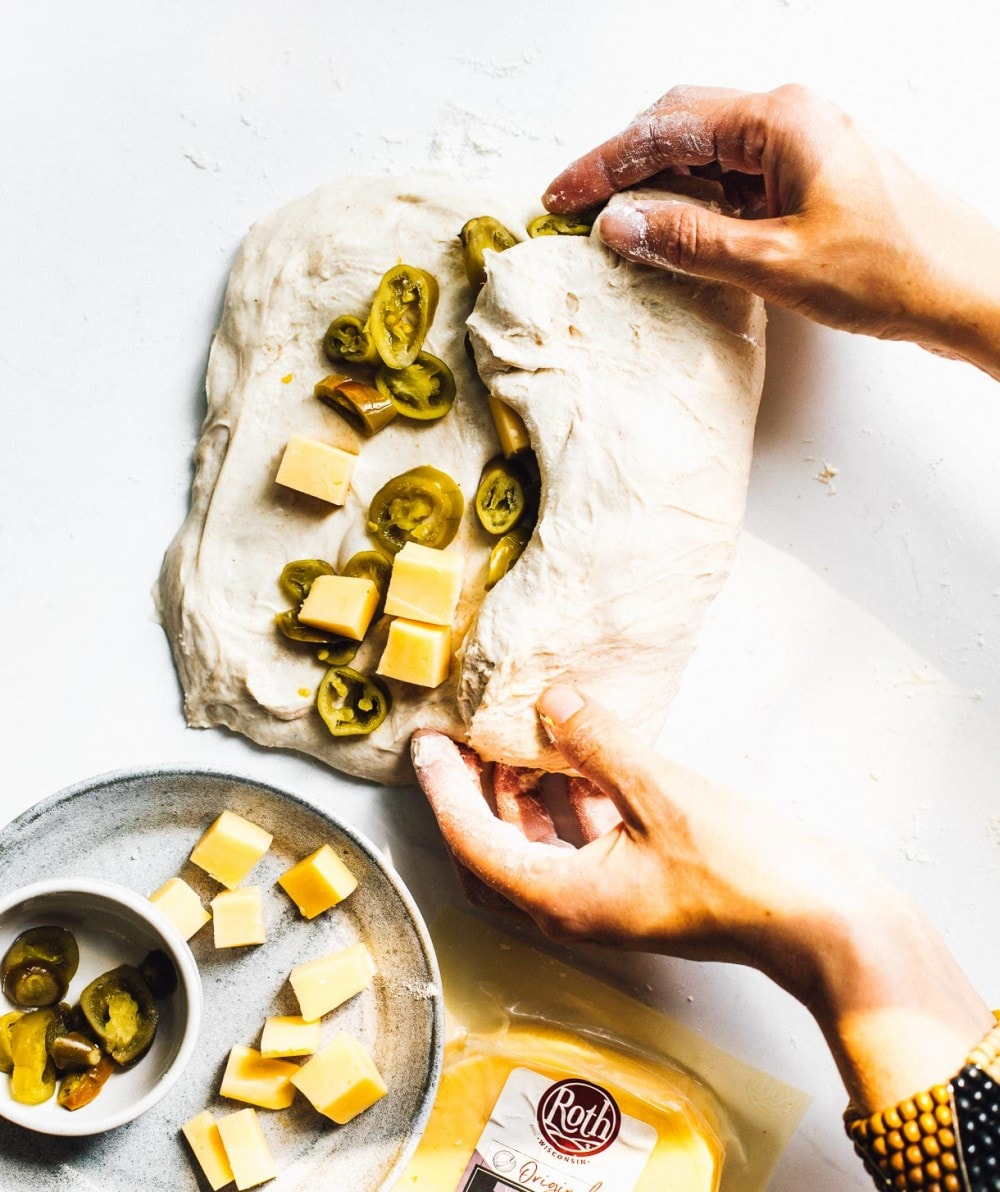 folding cheese and jalapenos into bread dough