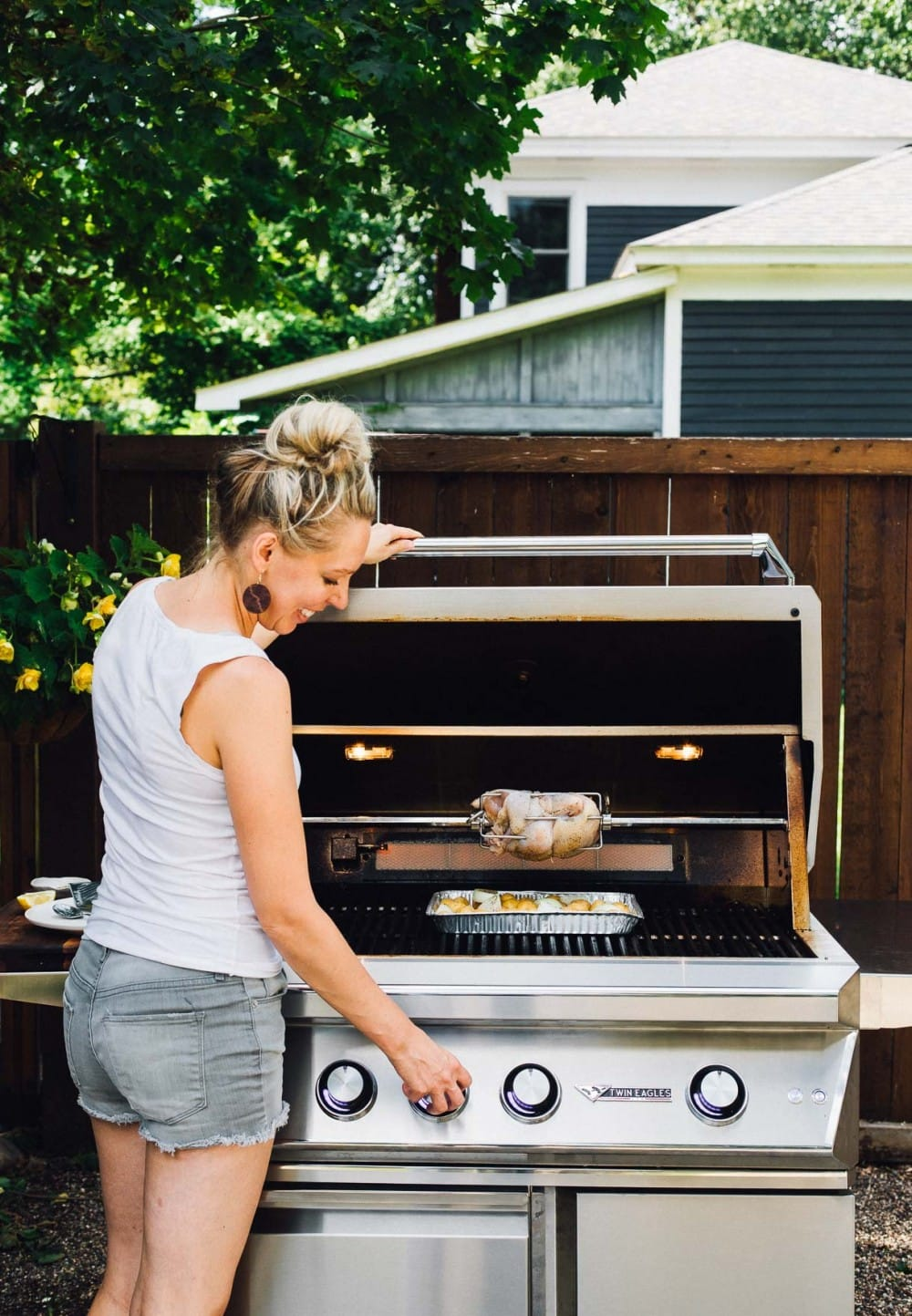 girl standing in front of a grill, with a chicken on a rotisserie
