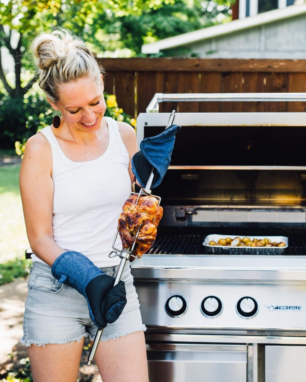 girl holding a rotisserie chicken attached to a spit, open grill in backround