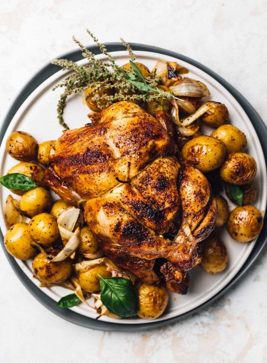whole chicken on a white plate with potatoes and onions underneath it, sprigs of basil tucked in