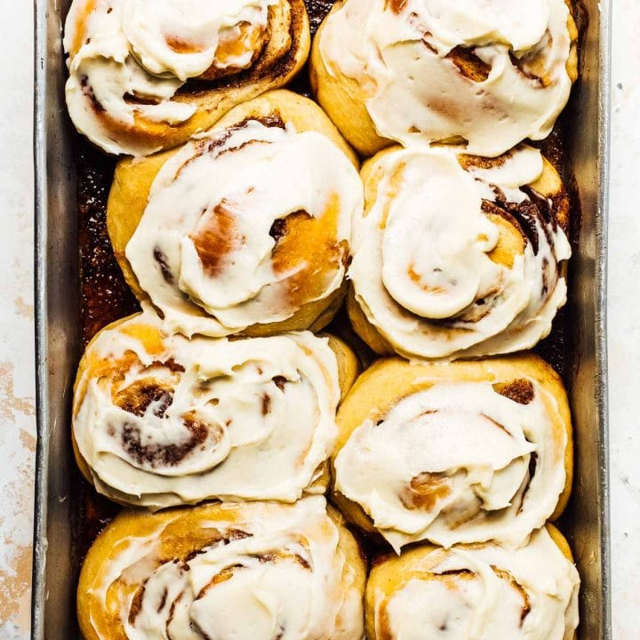 a pan of sourdough cinnamon rolls slathered with cream cheese frosting