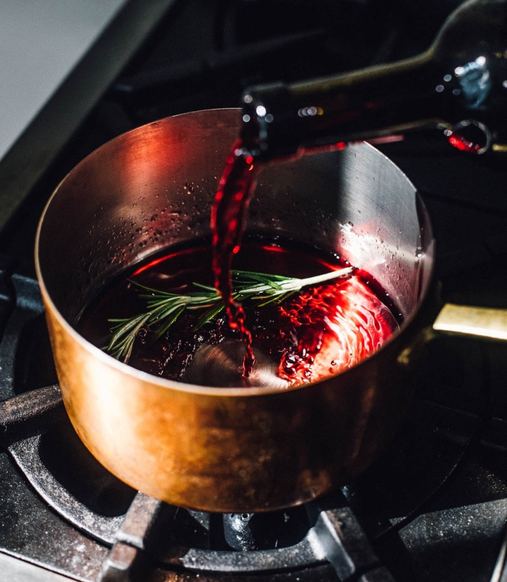 red wine being poured into copper kettle, rosemary also in the pan