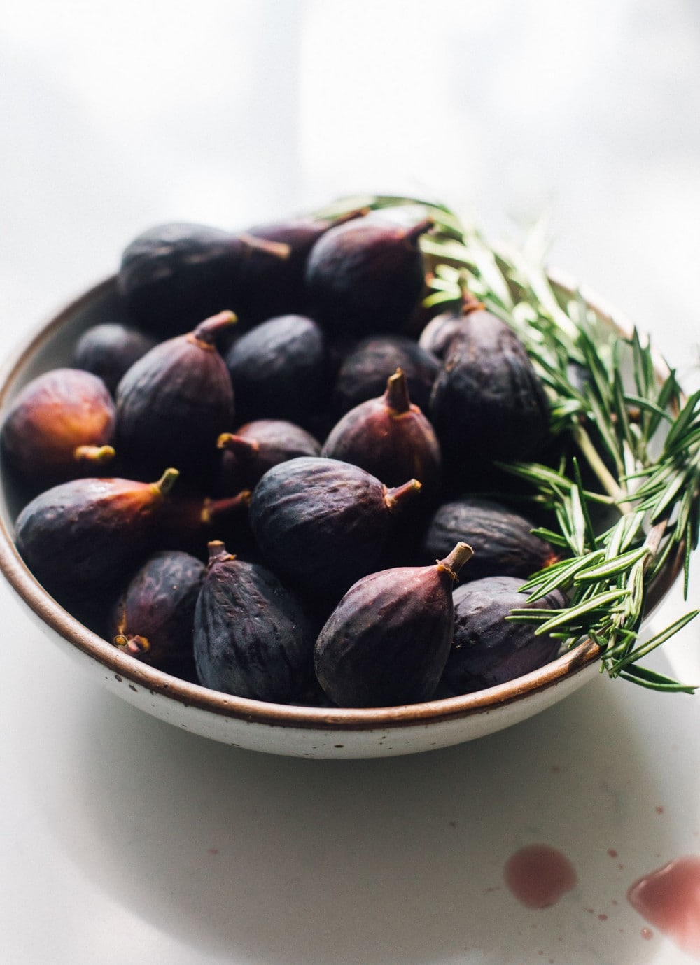 bowl of mission figs with rosemary sprigs sitting on the right side of bowl