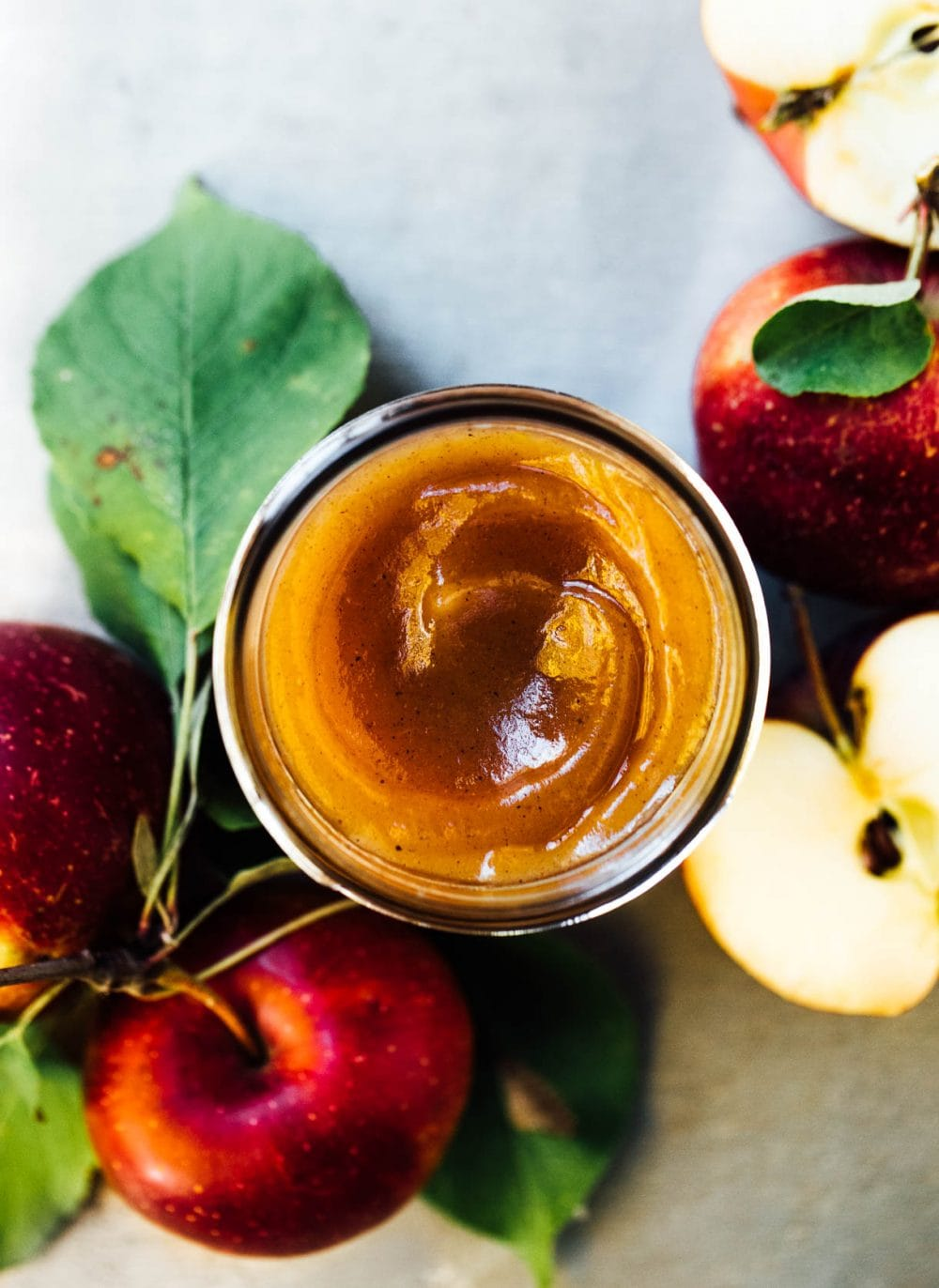apple butter in a glass jar with top off, apples surrounding jar