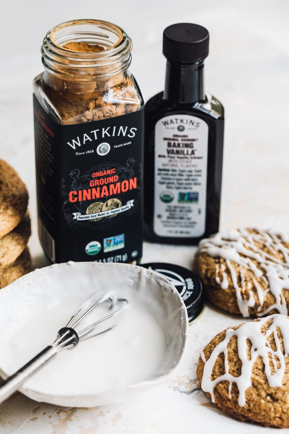watkins organic cinnamon and baking vanilla sitting by cookies