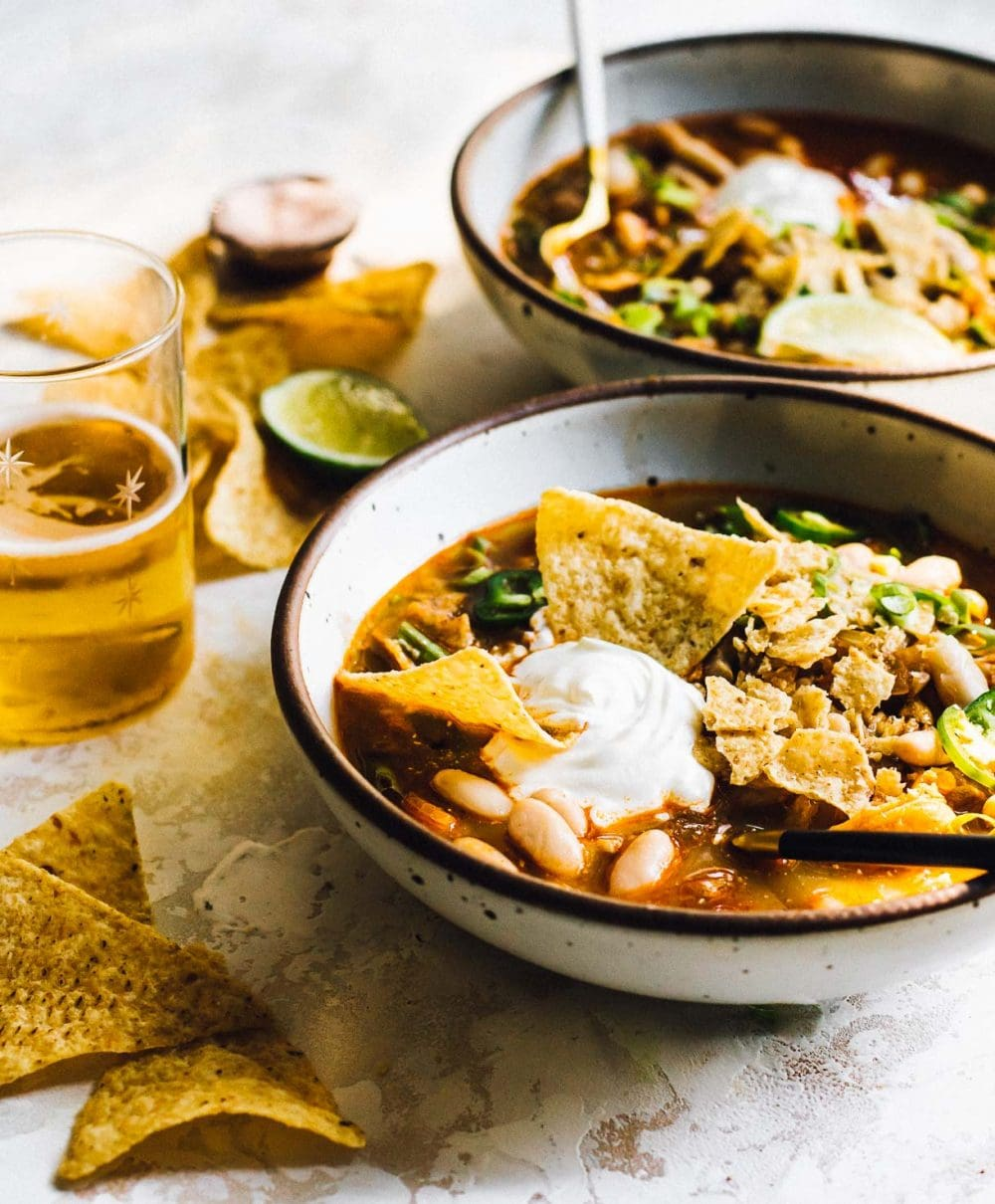bowl of green chili chicken soup with tortilla chips in it, dollop of sour cream on top, tortilla chips scattered around bowl and glass of beer to the left