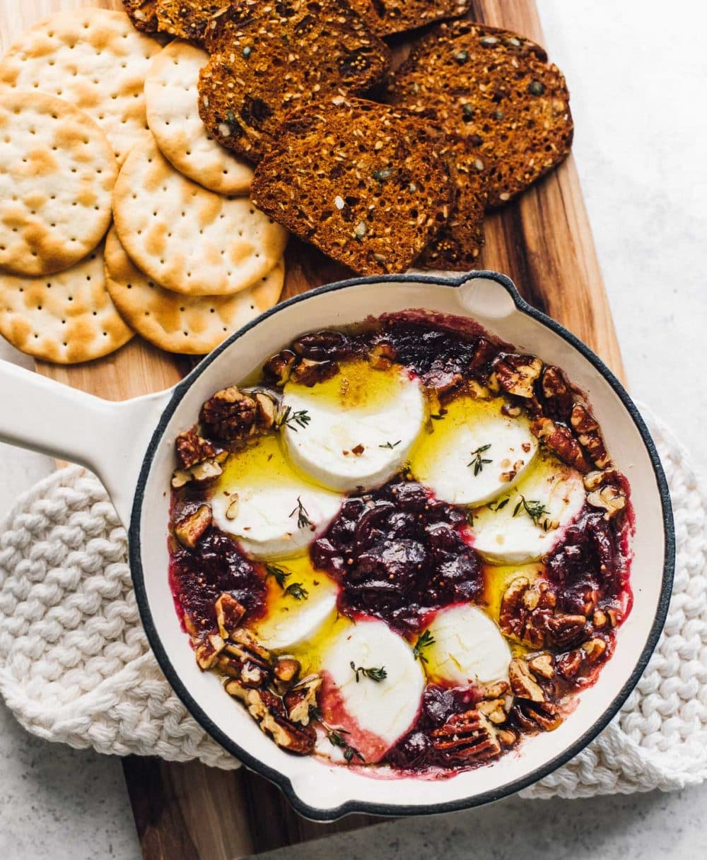 baked goat cheese in a small white cast iron skillet with fig jam and crackers surrounding the dish