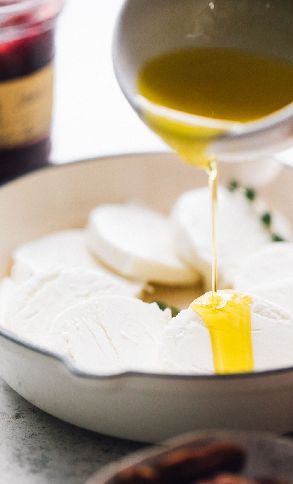 pouring olive oil over goat cheese in a white cast iron skillet