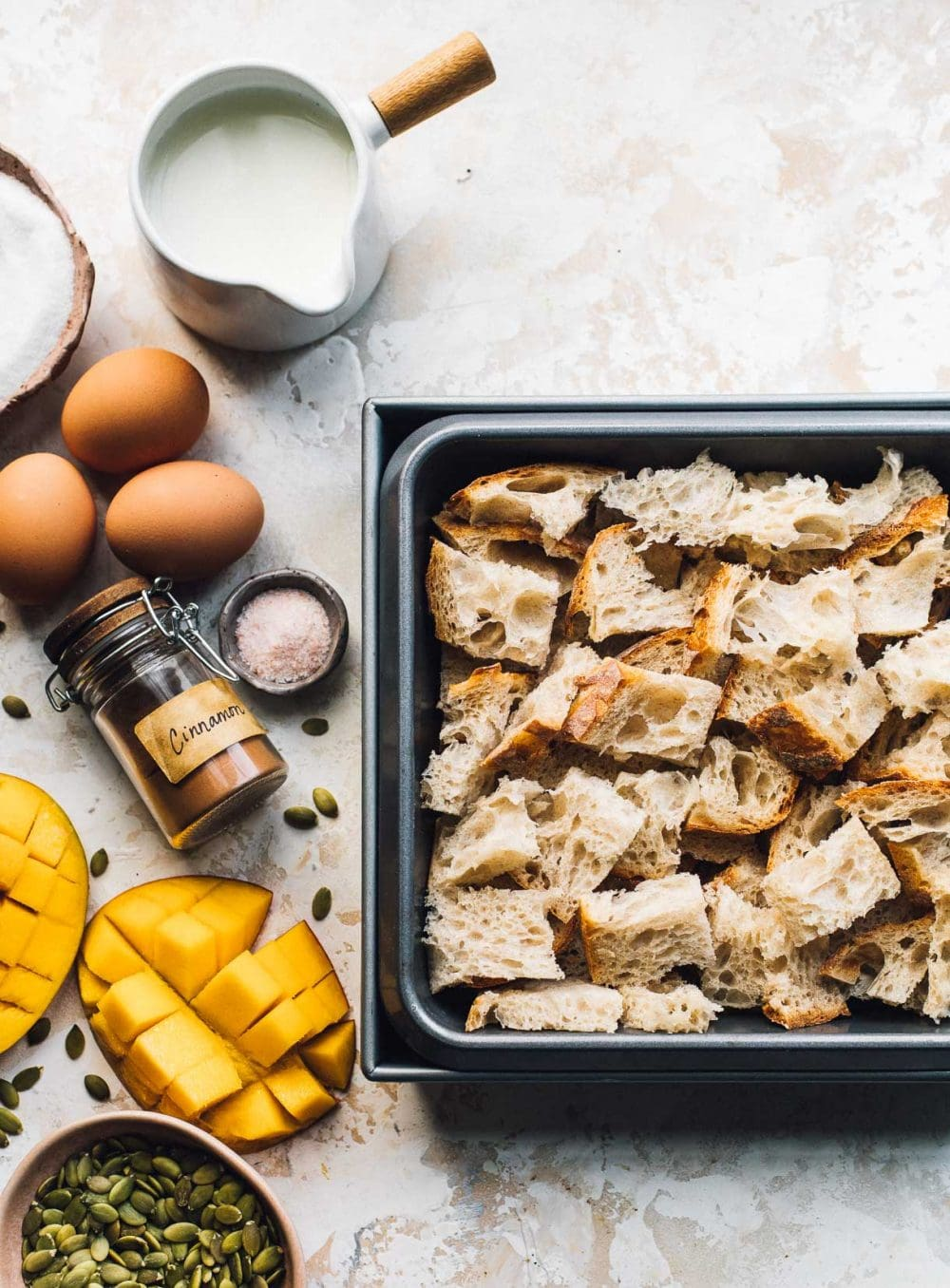 top down view of bread cubes in a pan surrounded by eggs, cinnamon, cream, and sugar, mango