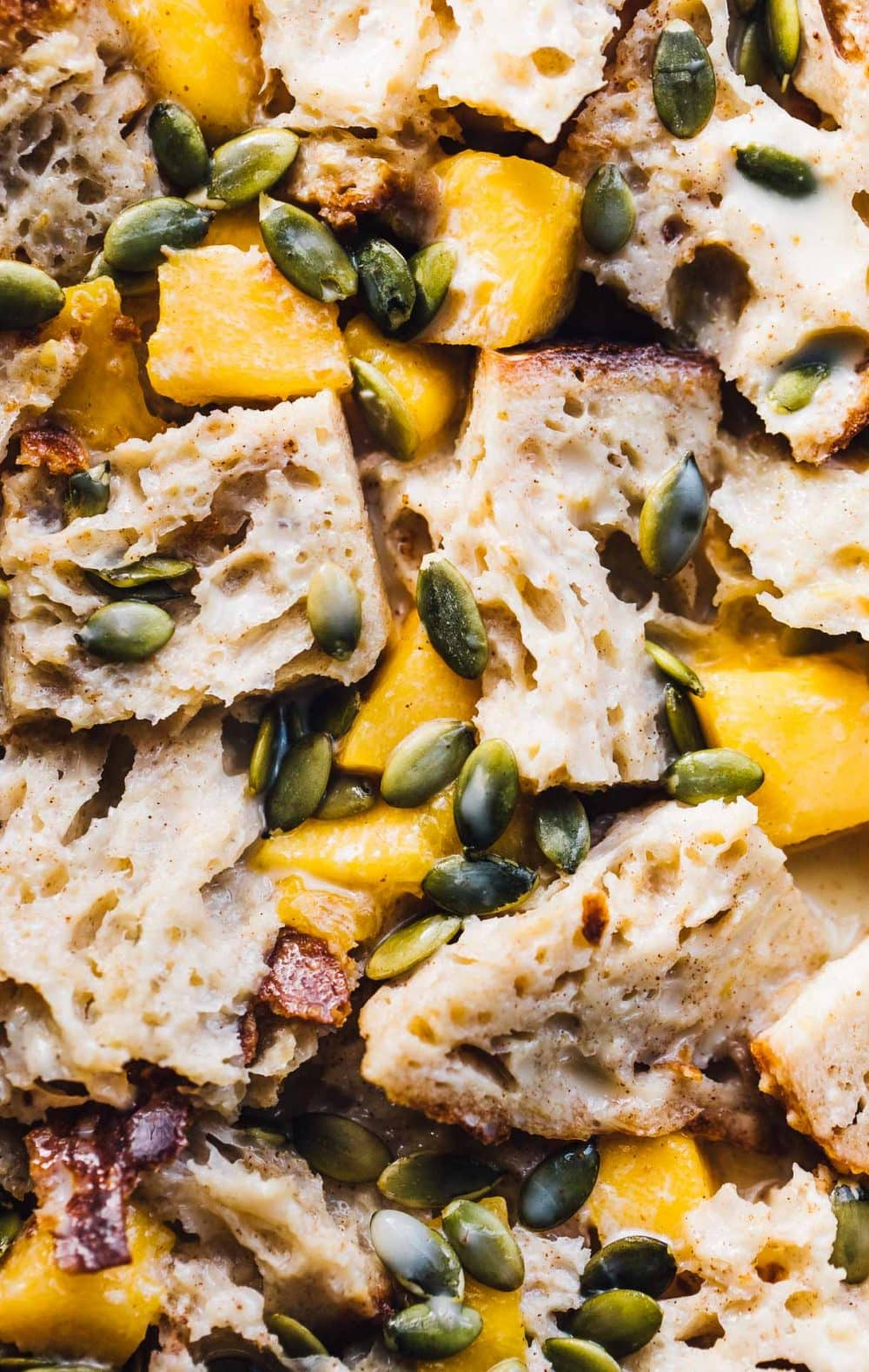 bread cubes with mangos and pepita seeds scattered on top