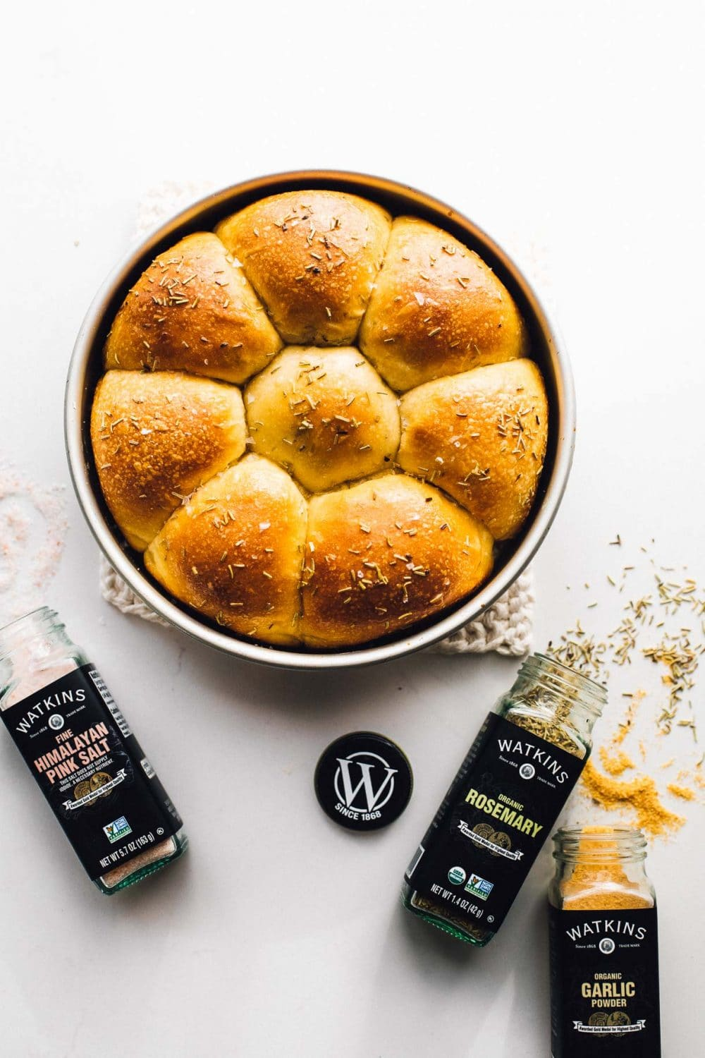 sourdough dinner rolls in a pan with spices surrounding them