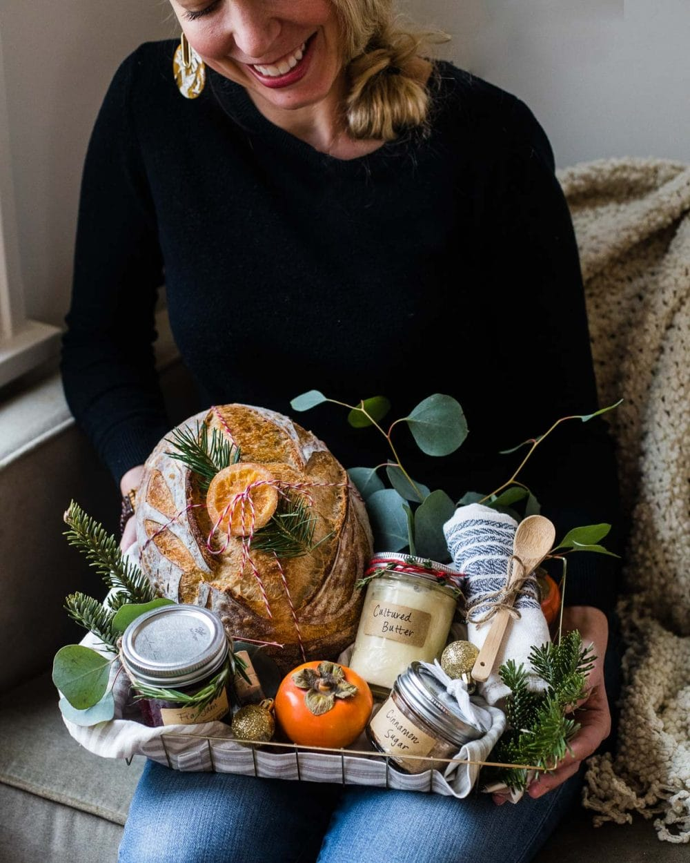 woman holding a gift basket with bread, jam, and butter