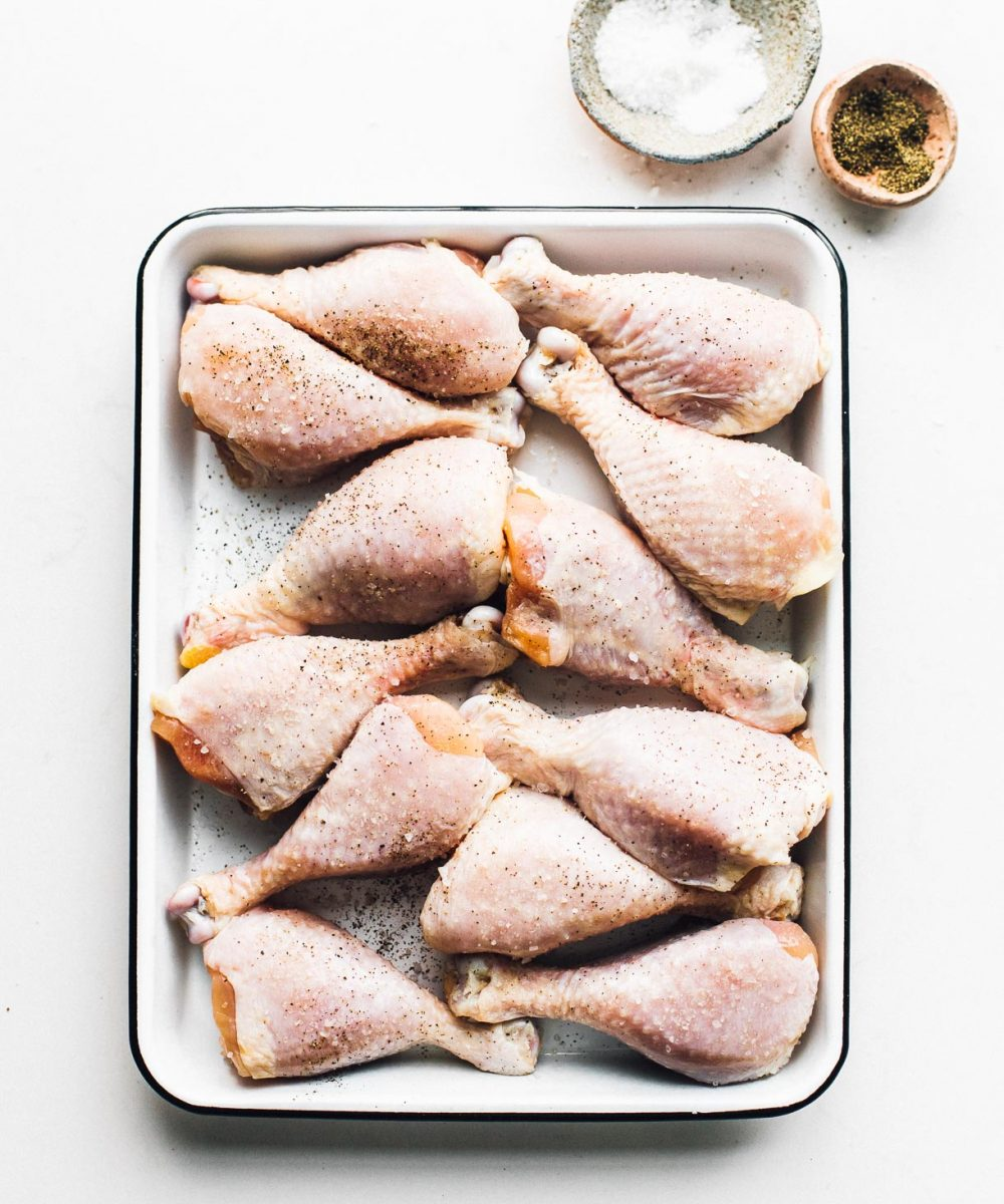 raw chicken drumsticks in a white enamel pan, with dishes of salt and pepper in top right of photo