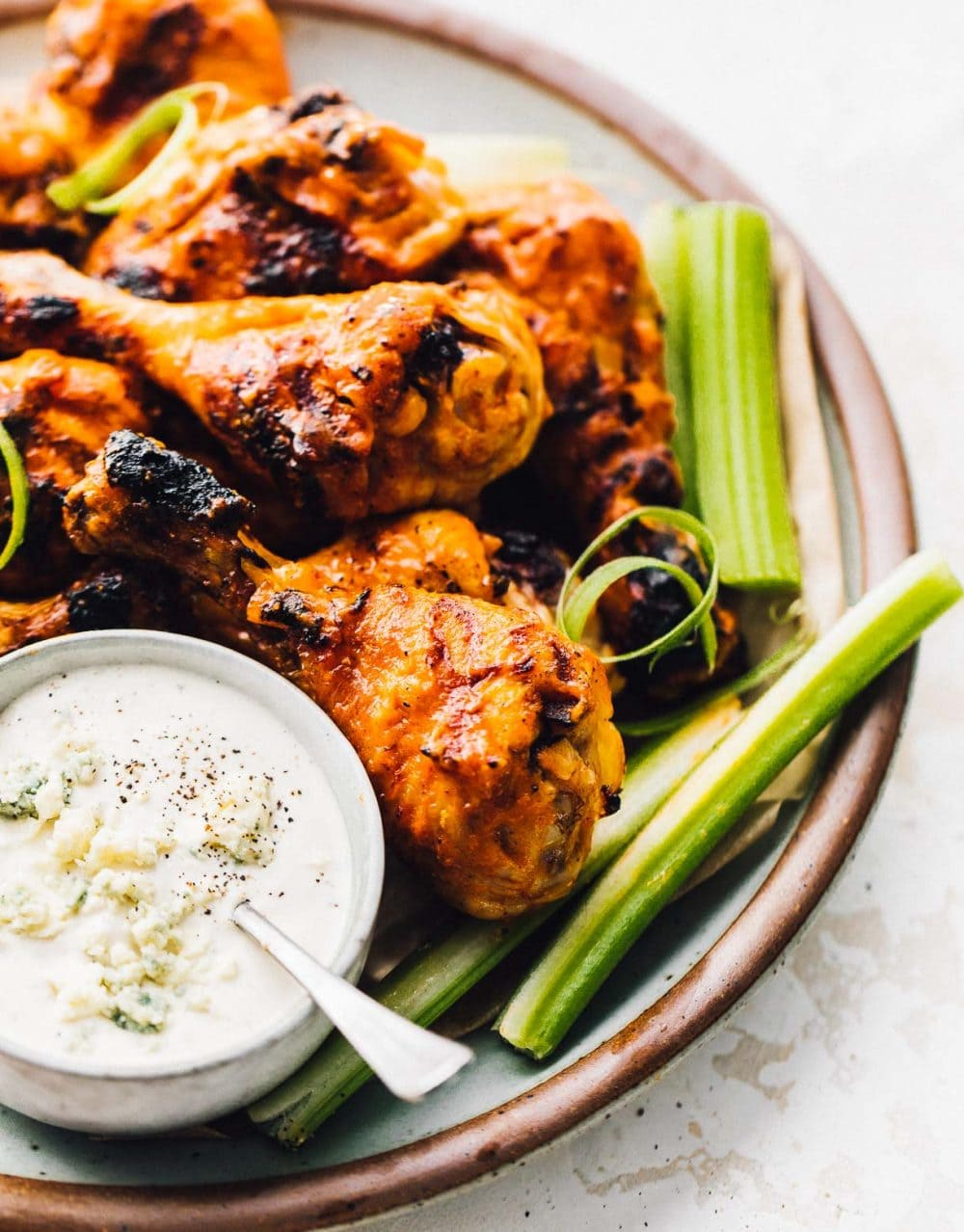 buffalo chicken drumsticks on a plate with celery and a small bowl of blue cheese