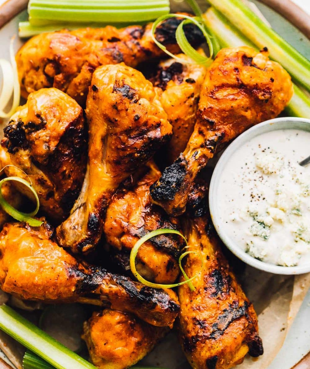buffalo grilled chicken drummies on a plate, with a blue cheese dressing in small bowl next to it.