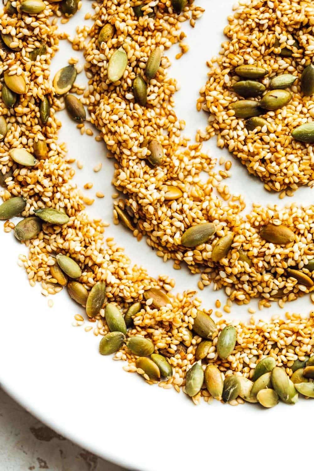 toasted sesame and pepita seeds in a swirled pattern on a white plate.