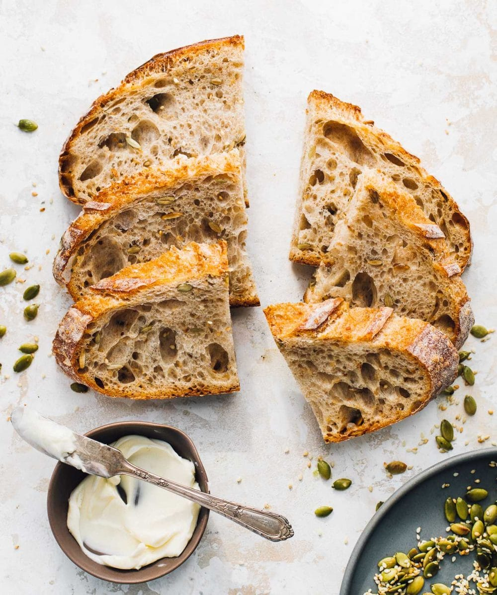 seeded sourdough bread slices cut in half, with a bowl of butter to it's bottom left, and on the bottom right a blue plate with toasted pepita seeds