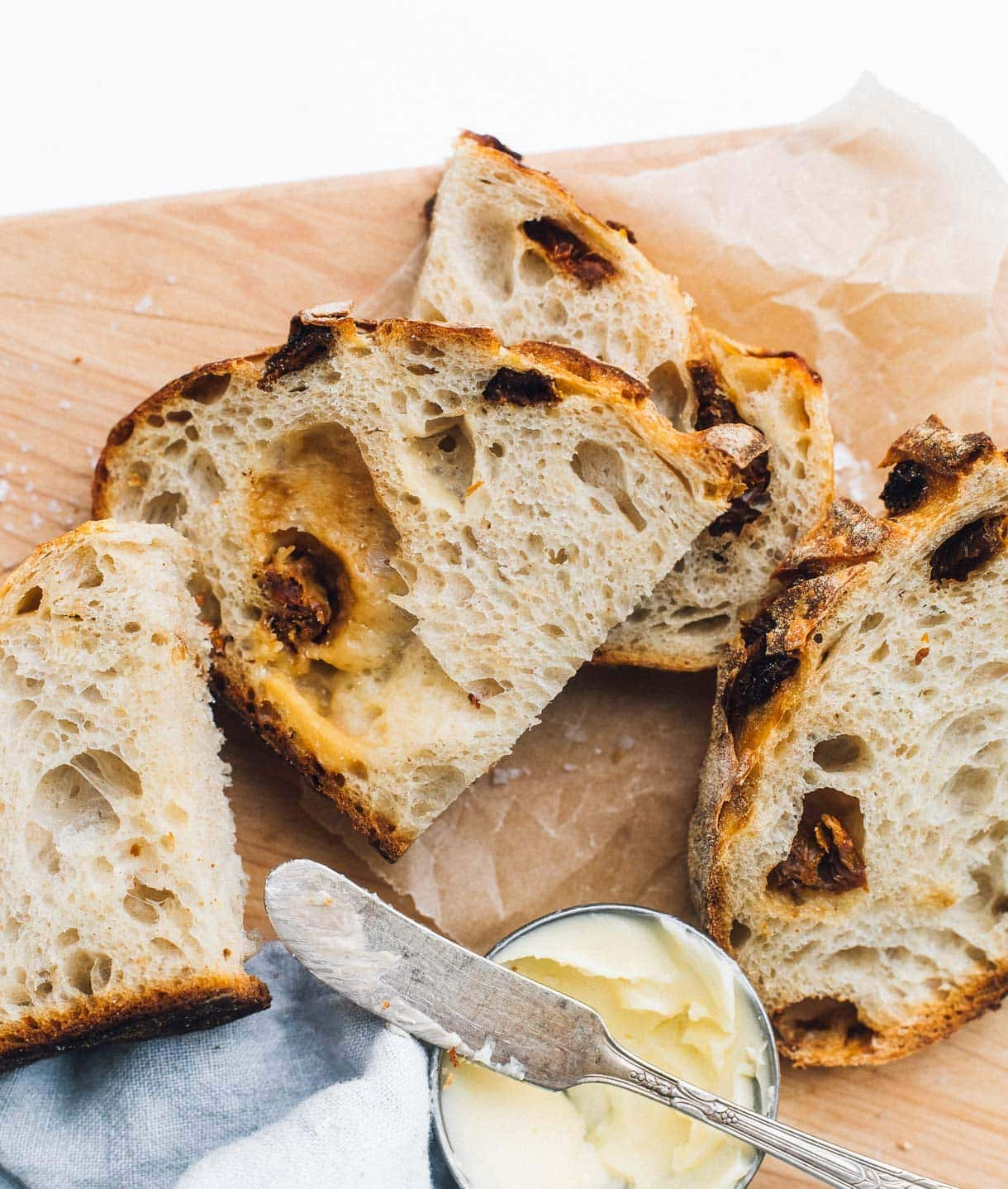 sun dried tomato and cheddar sourdough slices on a wooden cutting board, butter in a little silver dish.