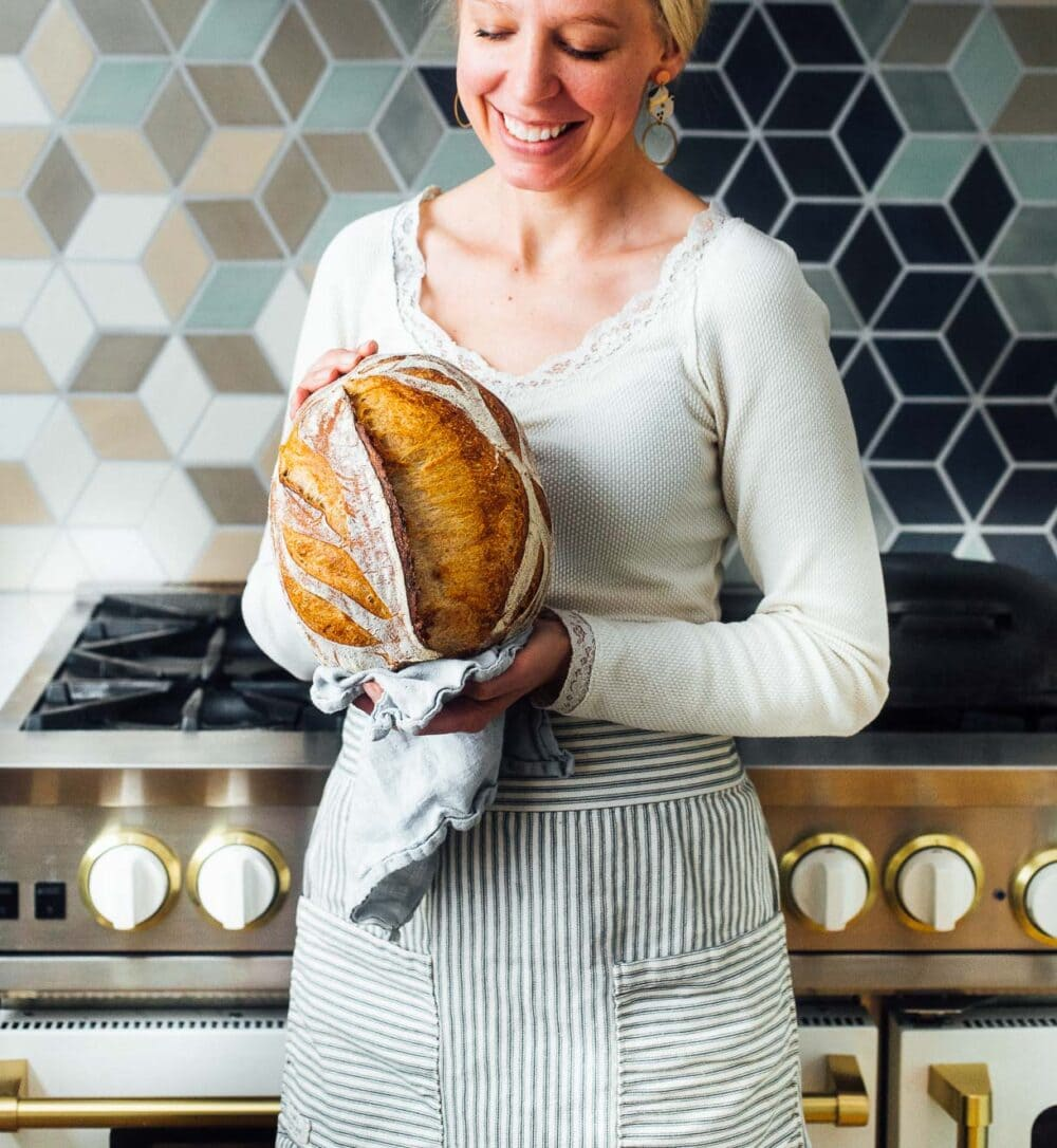 woman holding sourdough bread in front of her oven, she has a white shirt on.