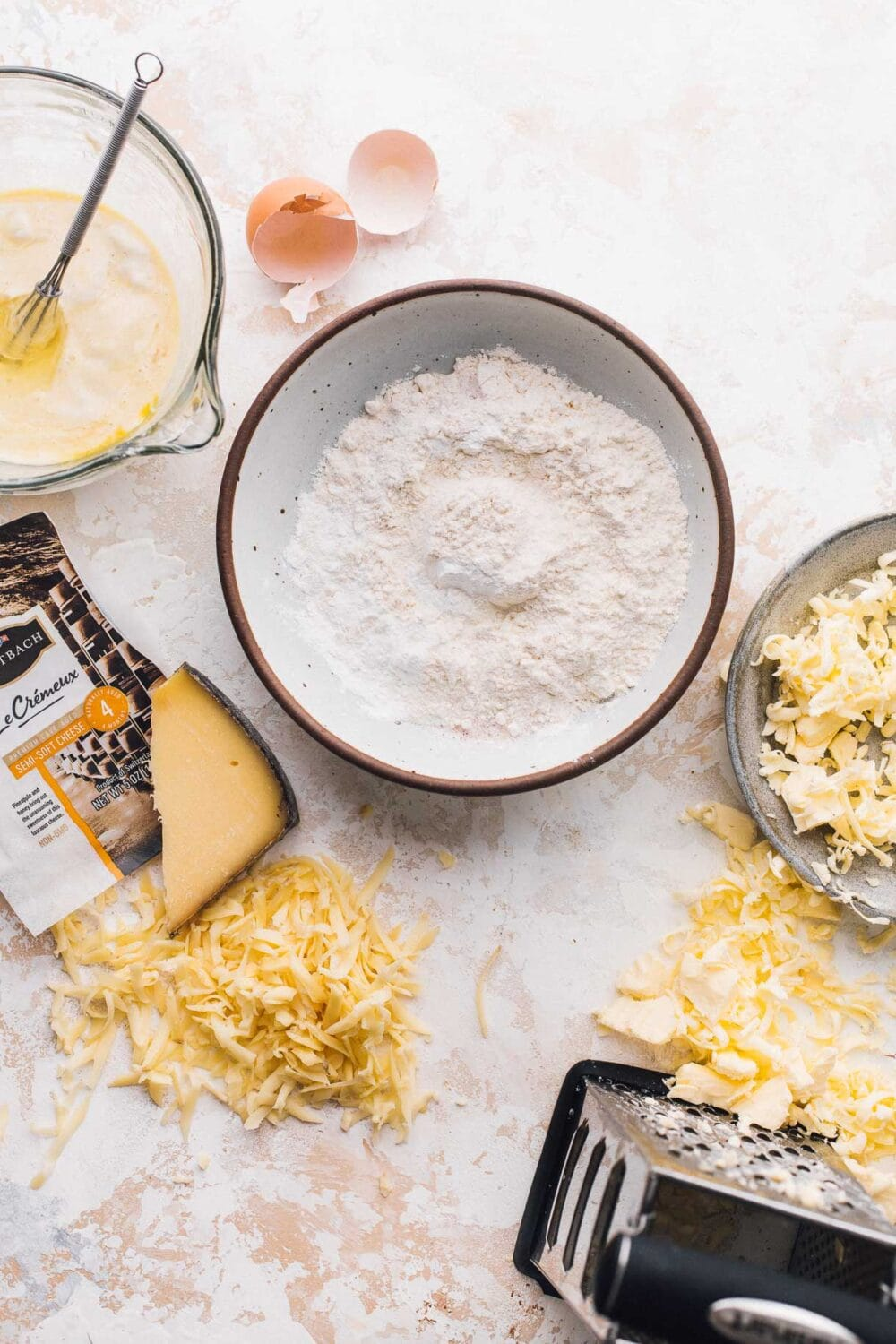 ingredients for sourdough discard biscuits laid out on a white surface, has a bowl of flour in the middle with grated cheese and butter to its side