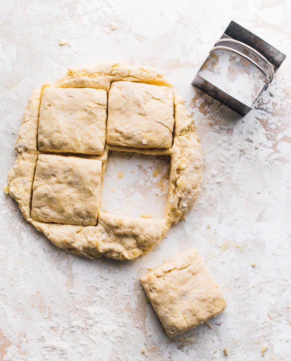 cutting out biscuits with a square biscuit cutter