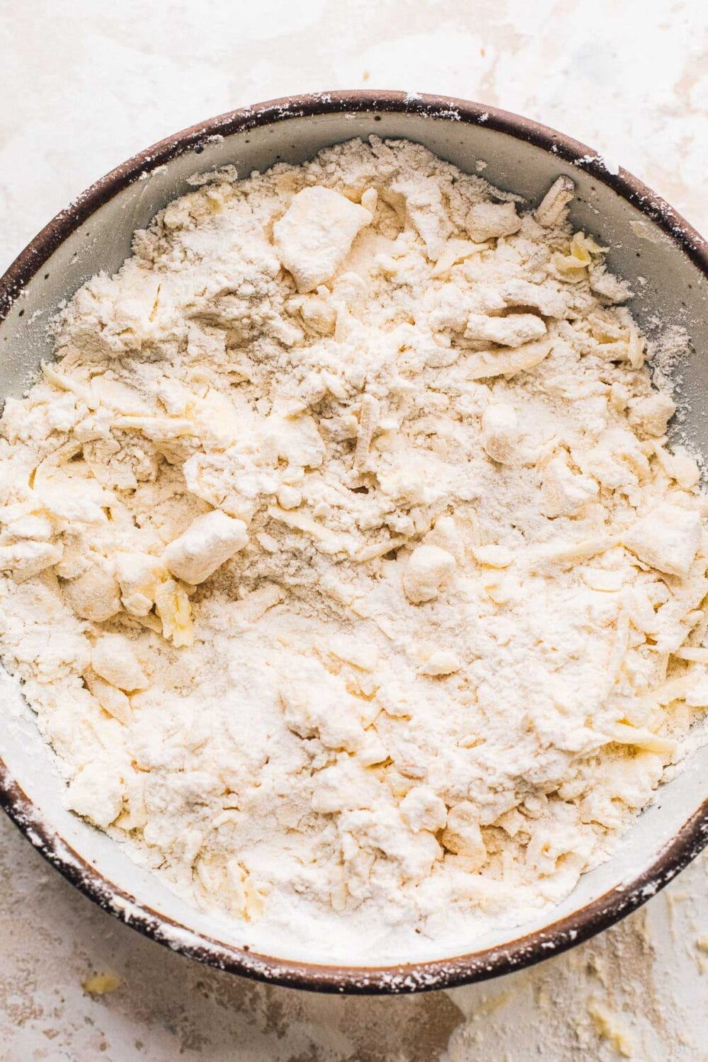 bowl of flour, grated butter, grated cheese in prep for making biscuits.
