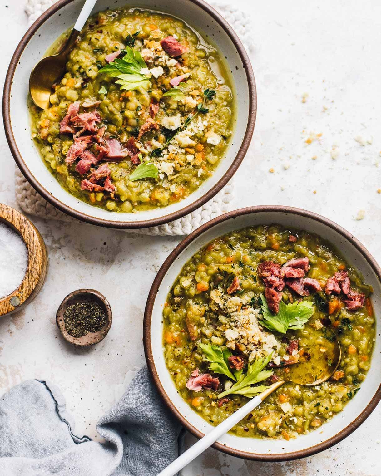 two bowls of split pea soup , with salt and pepper dishes to their left.