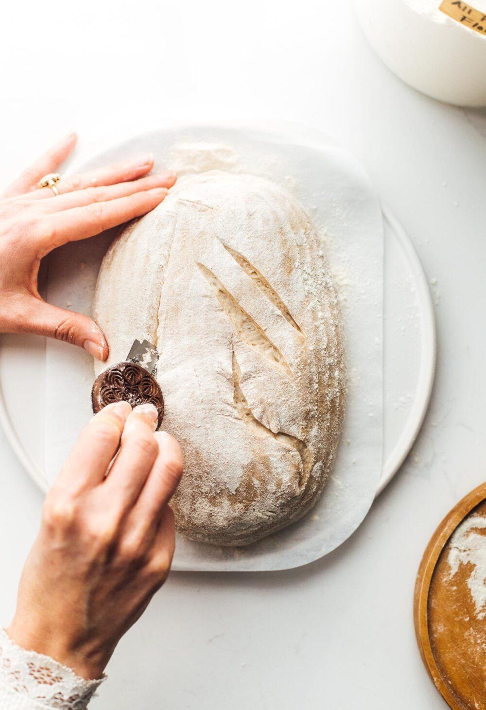 scoring sourdough bread on parchment paper