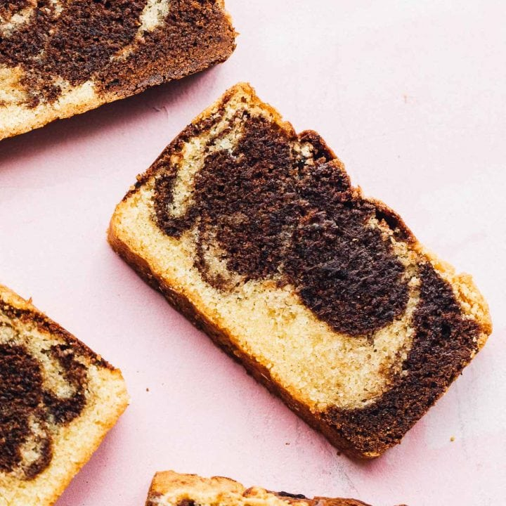 slices of gluten-free marble pound cake on pink background