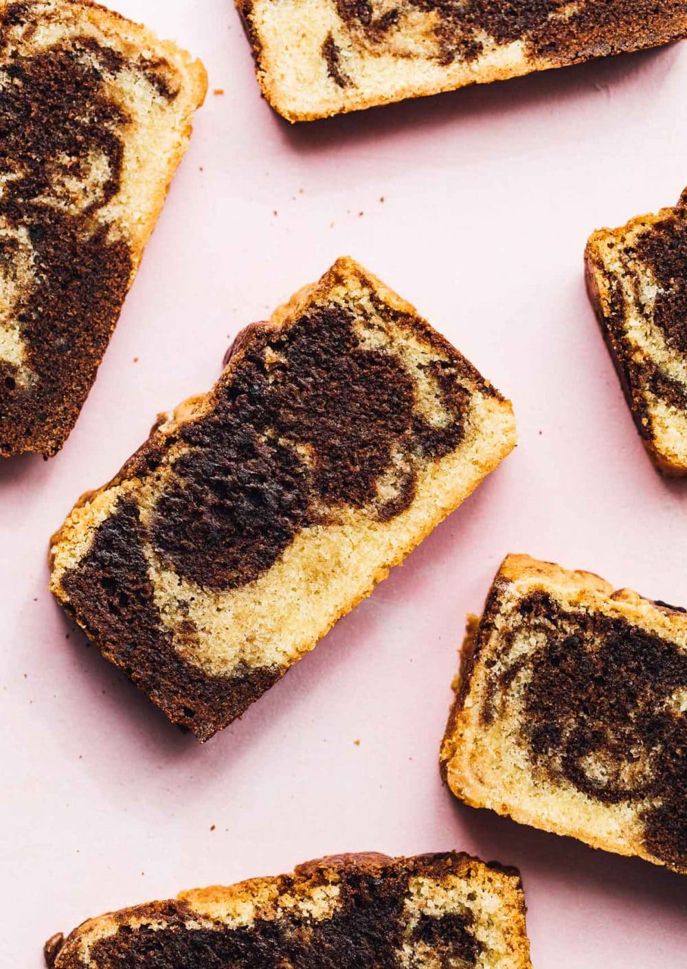 slices of marble pound cake on a pink backround