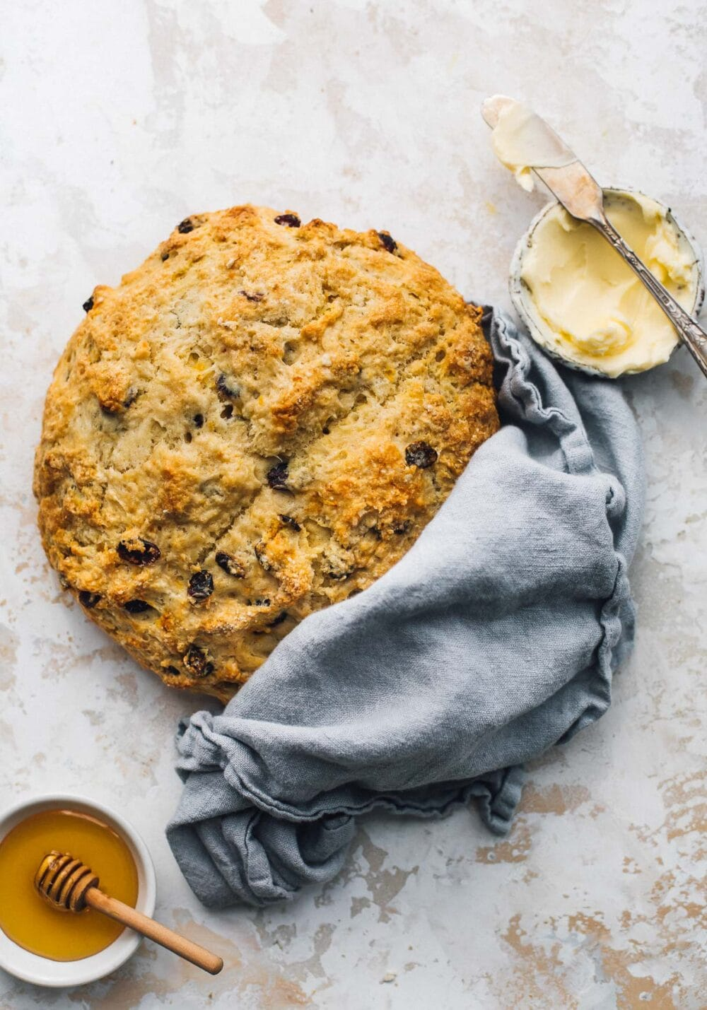 sourdough discard soda bread with a blue cloth wrapped around it, honey in a small bowl and butter in a small bowl next to it.