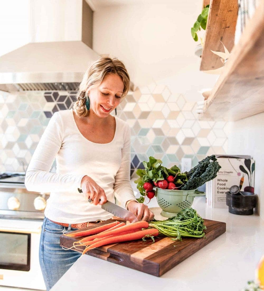 woman in kitchen, cutting carrots on a wooden cutting board