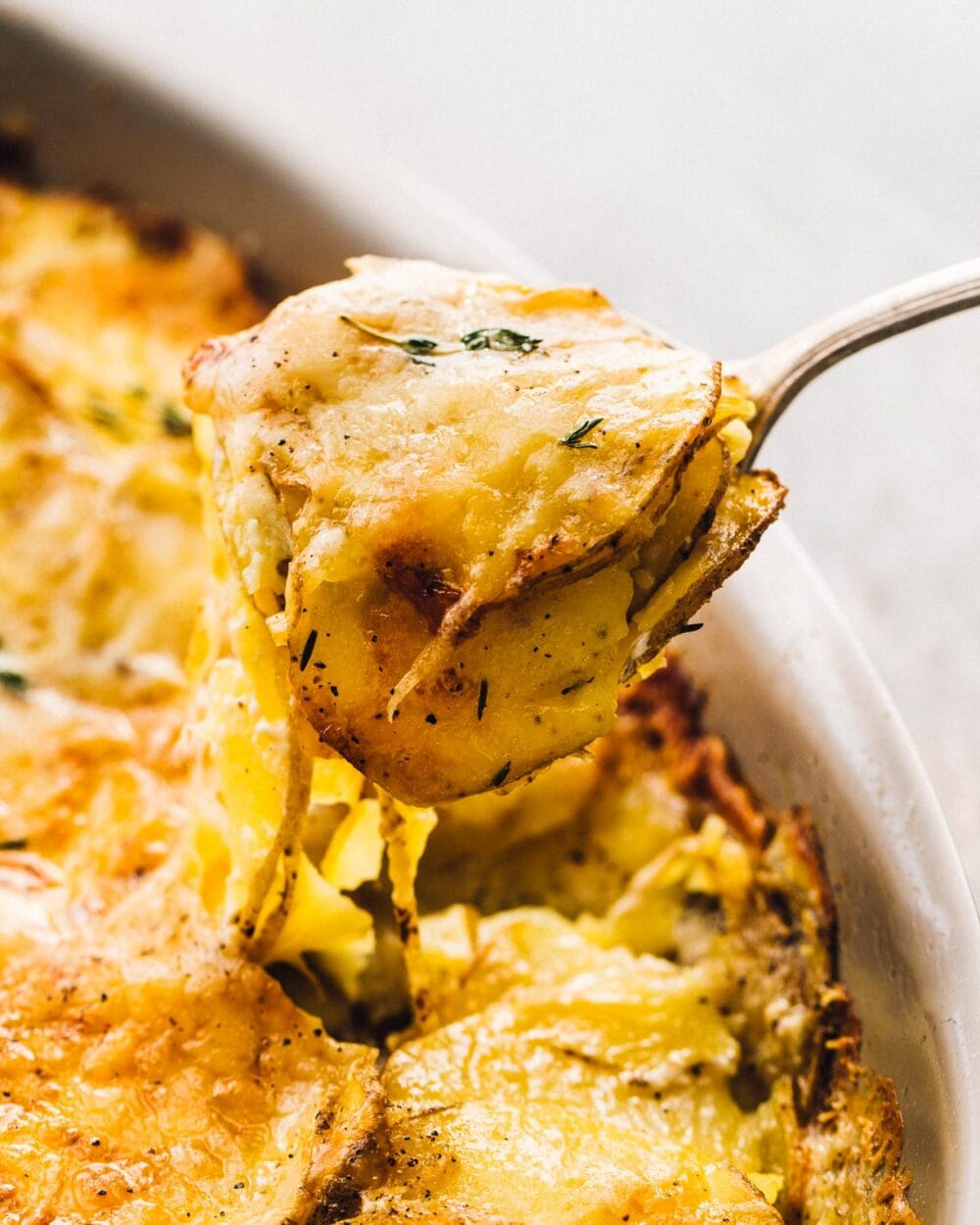 au gratin potatoes being scooped with a spoon