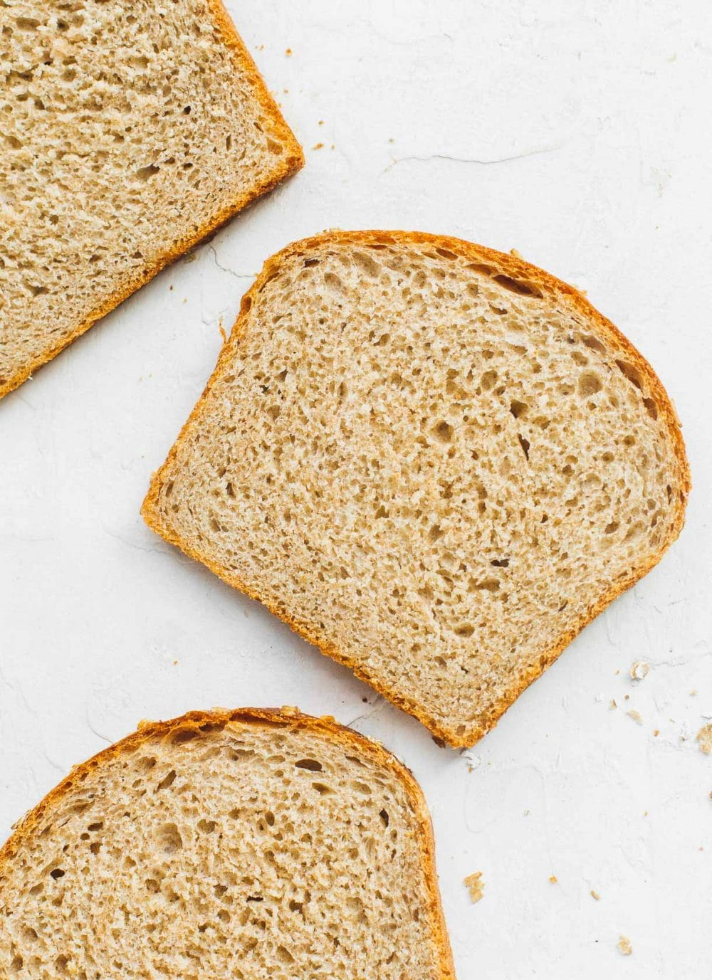 whole wheat sourdough sandwich bread slices laying on white backround