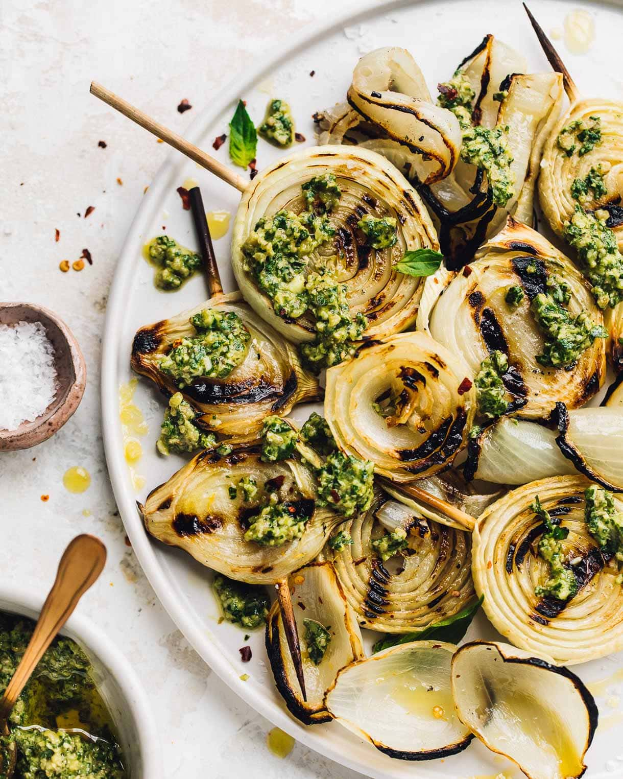 white plate holding grilled onions on skewers with pesto