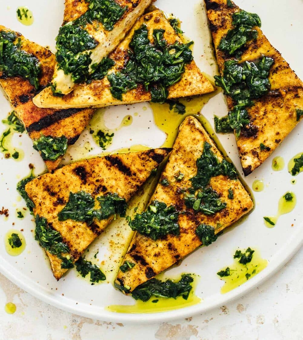 grilled tofu with green sauce on a white plate