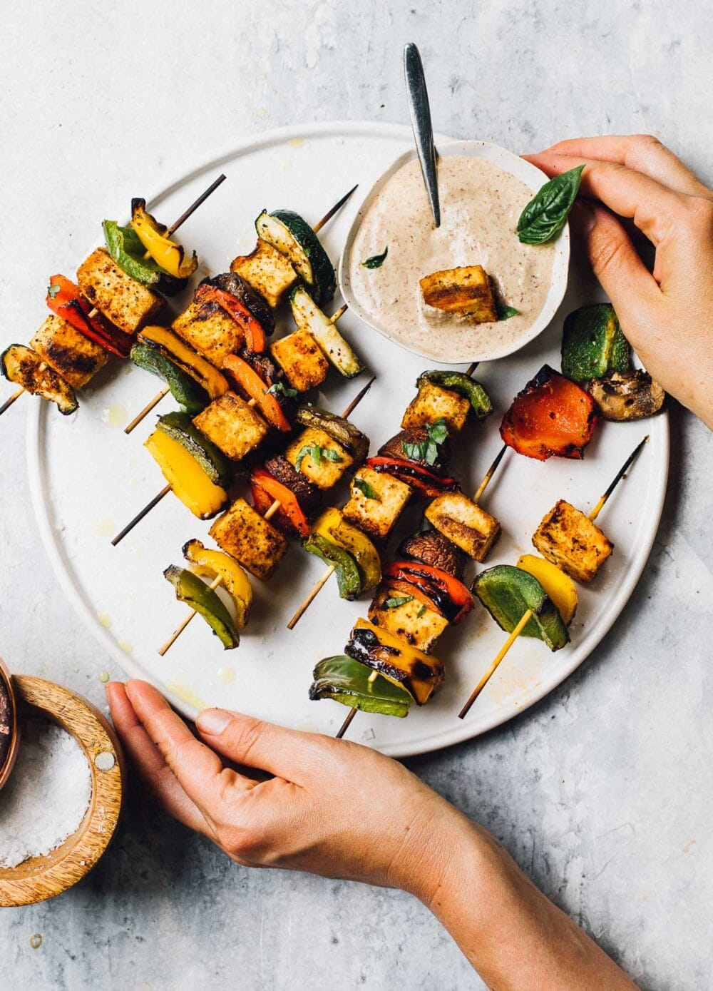 grilled veggie kabobs with dipping sauce on a white plate, woman holding the plate.