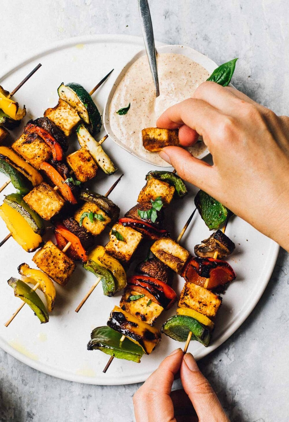 woman dipping tofu from a veggie skewer into dipping sauce