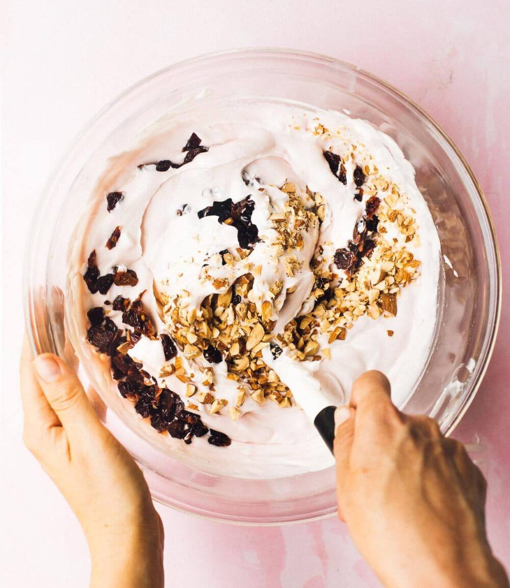 folding tart cherries and almonds into no-churn ice cream base, in a glass bowl.