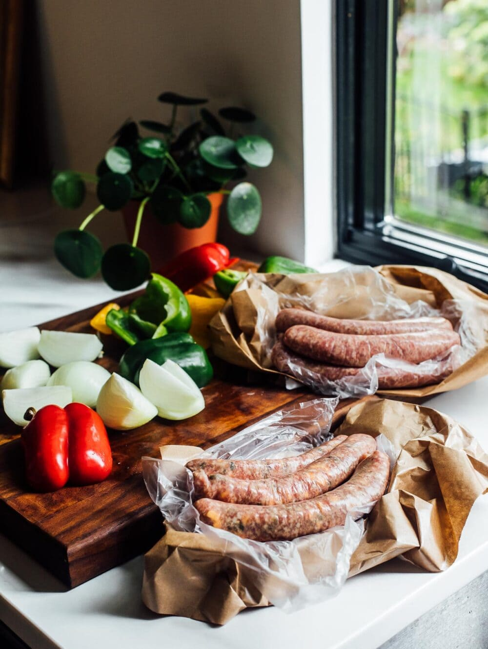 fresh brats sitting on a kitchen counter amongst a wooden cutting board with vegetables.