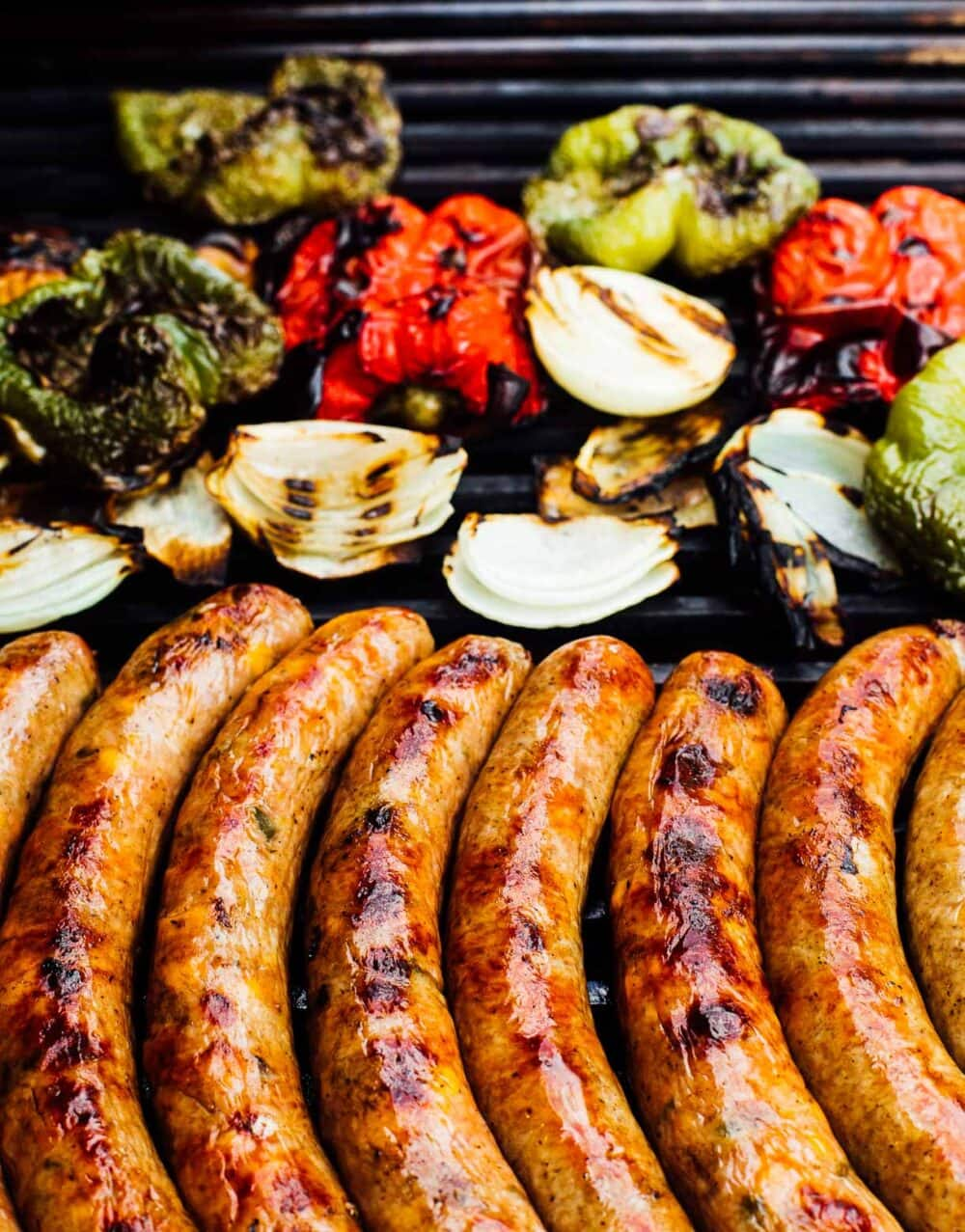 brats and peppers, onions, on a grill