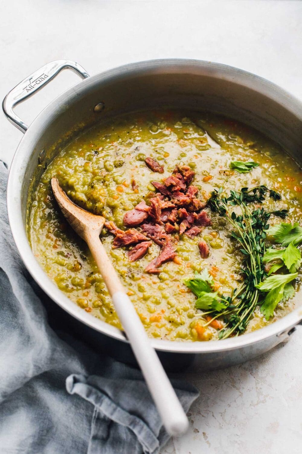 split pea soup in pot with herbs on top and wooden spoon.