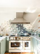 U-shaped galley kitchen with blue star white matte range, sage green cabinets