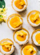 mango cheesecake bites scattered on a white surface, with fresh mango cheesecake topping