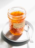 hot pepper jelly in a small glass canning jar with spoon to its right, both on a round plate