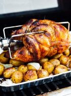 rotisserie chicken sitting on top of potatoes and onions in an aluminum pan