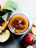 homemade apple butter in a glass jar with apples surrounding