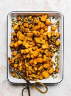 air fryer butternut squash in a white enamel pan with pepita seeds