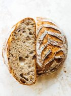seeded sourdough loaf cut in half, with one half crumb side up.
