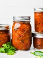 canned roasted salsa in ball mason jars, with cilantro next to it